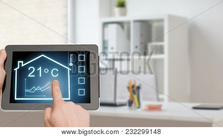 smart home and technology concept - close up of male hands pointing finger to tablet pc computer screen and regulating room temperature over office room background