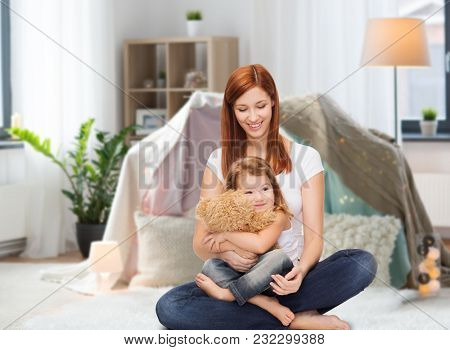childhood, parenting and relationship concept - happy mother with adorable little girl and teddy bear over kids room and tepee background