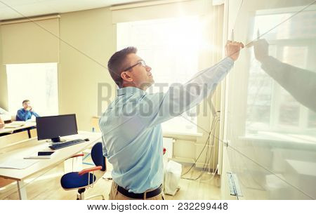 education, school, learning, teaching and people concept - teacher standing in front of students and writing something on white board in classroom