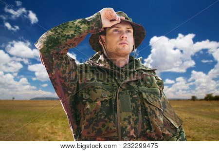 army, national service and travel concept - young soldier, ranger or traveler wearing military uniform and jungle hat over natural background and blue sky