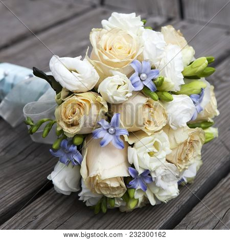 Wedding Bouquet Of Yellow And White  Roses And Blue Fresia  Lying On Wooden Floor