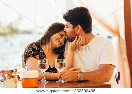 Young Couple In Love Sitting In A Cafe, Drinking Water, Having A Conversation And Enjoying The Time
