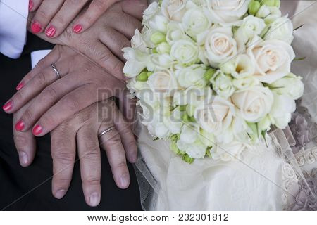 Hands Bride And Groom With Rings. Wedding Bouquet Of Pink And White  Roses And Fresia.