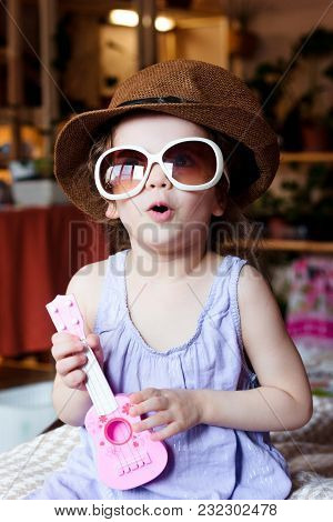 Little Kid Girl Having Fun With Toy Guitar In Arms And Sunglasses On Face