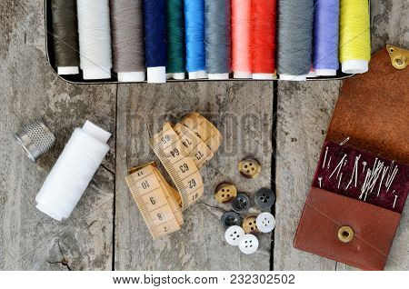 Multi-colored Spools Of Thread, Measuring Tape, Sewing Needles And Buttons On A Wooden Table. Backgr