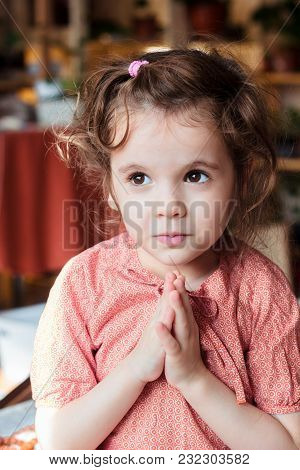 Little Kid Girl Sitting And Praying To God.
