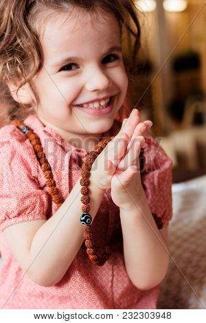 Little Kid Girl Holding Hands In Namaste Mudra And Smiling