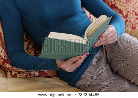 Beautiful Girl Is Reading A Book In The Bedroom, On The Bed. Concept Of Home And Comfort.