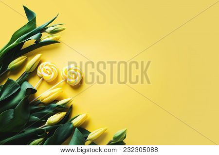 Yellow Tulips With Lollipop Candy Over Yellow Background, Border, Copy Space