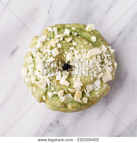 Matcha And White Chocolate Donut With Colorful Glaze And Sprinkles On Marble Surface