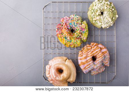 Variety Of Colorful Old Fashioned Fried Gourmet Donuts On A Cooling Rack With Glaze