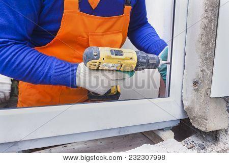 The Worker Installs Plastic Windows And Doors