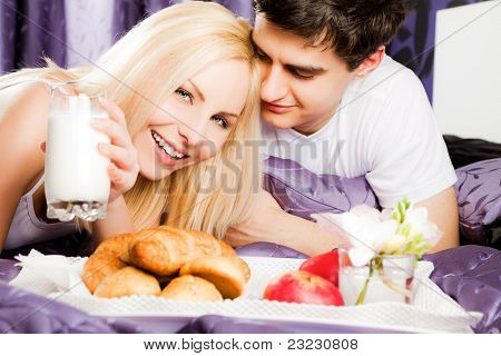 Happy young couple lying and having breakfast in bed, woman looking at camera