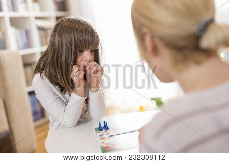 Mother And Daughter Sitting In A Playroom, Playing A Ludo Game
