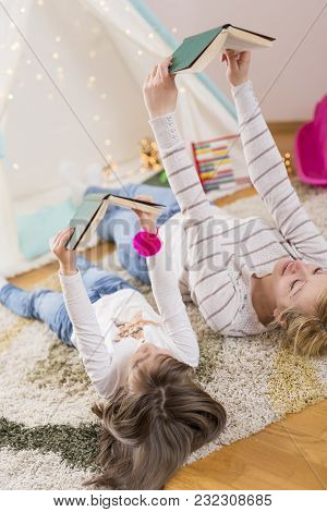 Mother And Daughter Lying On A Playroom Floor, Reading Books