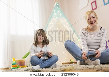 Mother And Daughter Sitting On The Floor In A Playroom, Playing Video Games And Having Fun. Focus On