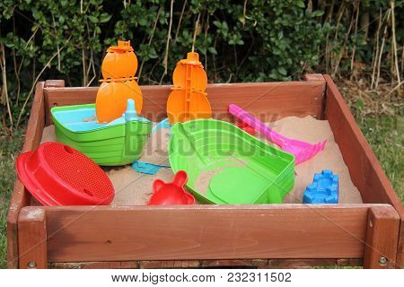 A Collection Of Plastic Toys In A Garden Sandpit.