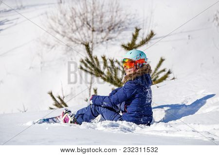 Photo Of Athlete In Helmet With Snowboard Sitting At Fir -tree On Winter Day