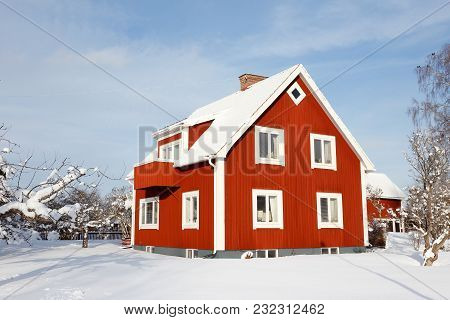 Two Stories Swedish Older Red Family House With Basment With A Snow Covered Garden During The Winter