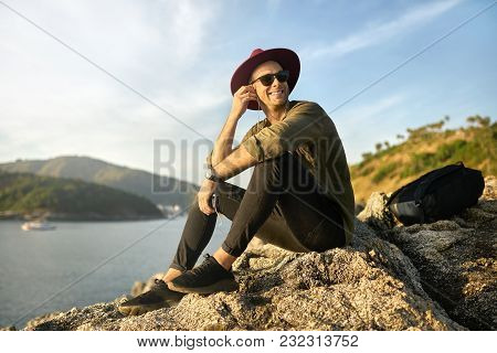 Nice Smiling Guy In Sunglasses Is Listening Music While Sitting On The Rocky Cliff On The Sunny Back