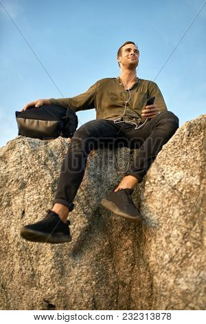 Cheerful Man With A Black Backpack Sits On The Rocky Cliff On The Sky Background. He Wears Dark Jean