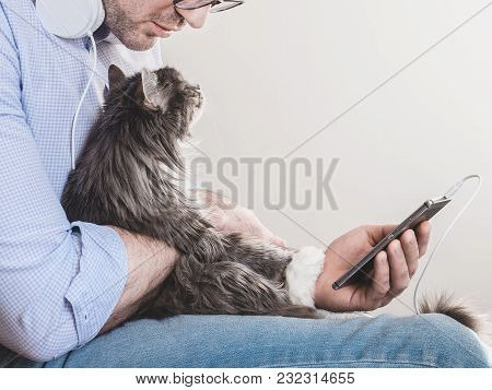 Handsome Man In Headphones And With A Mobile Phone, Gently Holding A Cute Kitten On His Hands. Peopl