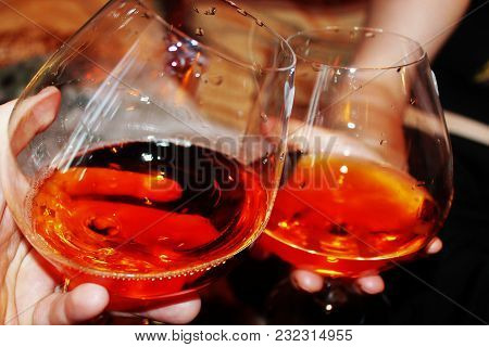 Two Glasses Of Wine In His Hands