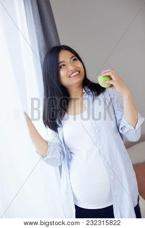 Beautiful Young Asian Pregnant Woman Stands By The Window And Holds An Apple. Pregnancy. Health. Mot