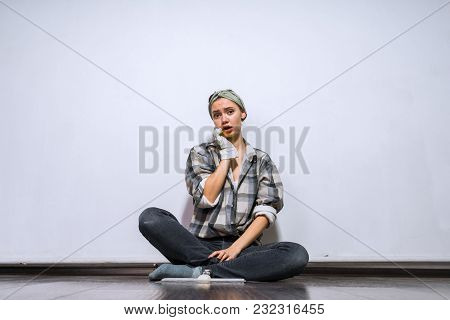 Sad Young Girl Sitting On The Floor In Her New Apartment, Wearing Rubber Gloves, Tired Of Doing Repa