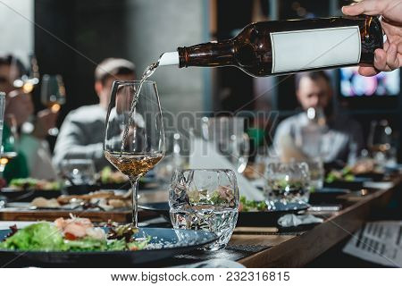 Served Table At Wine Tasting. Sommelier Pouring Wine From A Bottle Into Glasses