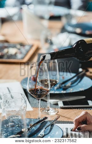 Served Table At Wine Tasting. Sommelier Pouring Red Wine From A Bottle Into Glasses