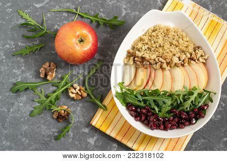 Vitamin Vegetarian Salad With Quinoa, Apples, Arugula, Pomegranate Seeds And Walnuts. Dressed With V