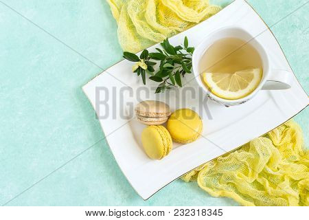 Yellow Macaroon With Citrus And Vanilla Cream, Tea With Lemon On White Plate. Delicious Almond Cooki
