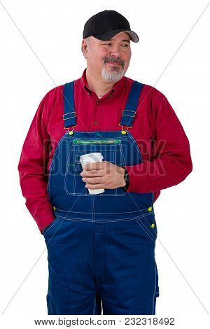 Thoughtful Farmer Or Worker Looking To The Side With A Quiet Smile While Standing Holding A Cup Of T