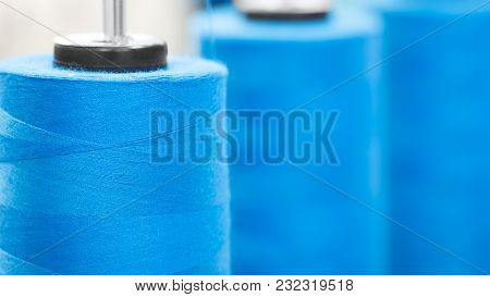 Close-up Bobbins With Blue Colored Thread For Industrial Textile Machines, Blue Textured Web Banner