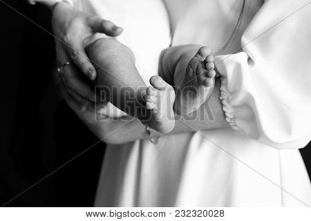 The Male And Female Hand Hold The Heels Of The Baby
