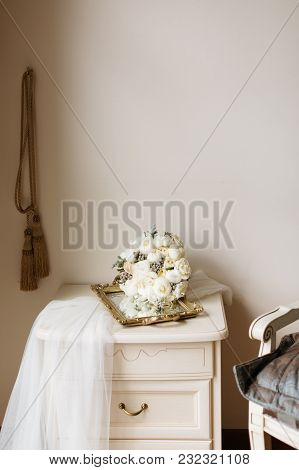 Bridal Morning Interior Composition With White Veil, Wedding Bouquet And The Nightstand.