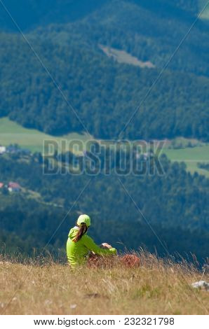 Young Woman Enjoying The View From A Hilltop
