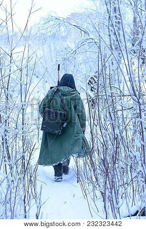 Rear View Of Fisherman Walking Among Bushes In Winter