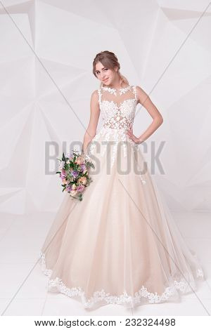 Beautiful Woman Holding A Bouquet Of Flowers Wearing In Luxurious Wedding Dress Isolated On Backgrou