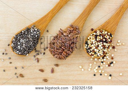 Dried Chia seed, Linseed flaxseed, Quinoa seed tri-color blend on wooden spoon, wood background