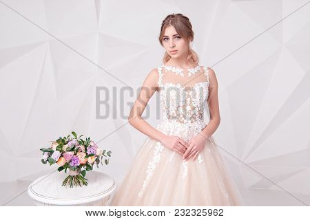 Beautiful European Woman Standing Near Table With Flowers Wearing In Luxurious Wedding Dress On Back