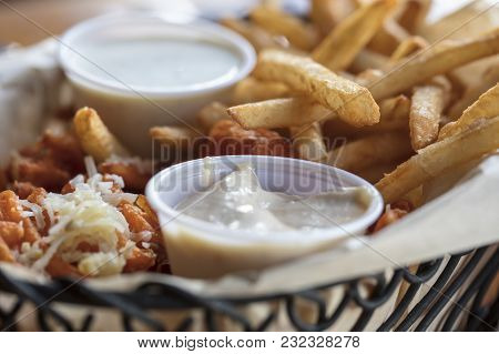 Wire Basket Filled With Sweet Potato And French Fries Served With Aioli Sauce And Ranch Dressing