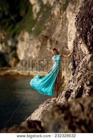 Beautiful Slim Woman Model In Turquoise Long Dress, Standing On Wild Rocks Of Ireland, Next To The S