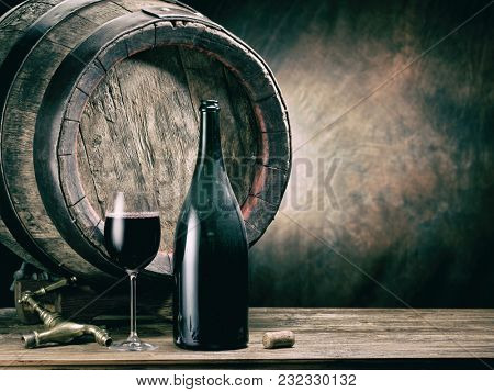 Glass of red wine and wine bottle. Oak wine keg at the background.