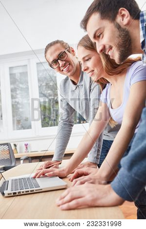IT consultant with colleagues at a laptop Computer in start-up business
