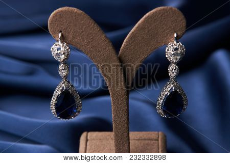 Beautiful Platinum Bracelet And Earrings. Luxury Women Jewelry With Diamonds And Sapphire On Blue Si