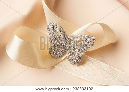 Brooch In Shape Of Butterfly With Diamonds On Peach Satin Background. Luxury Female Jewelry