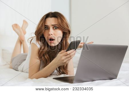 Portrait of a confused young woman holding mobile phone while lying in bed at home with laptop computer