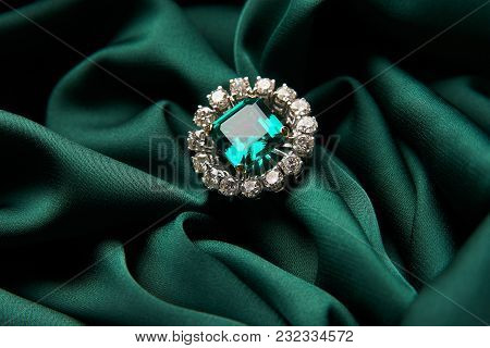 Diamond Ring And Earrings With Emerald On A Green Silk Background. Luxury Female Jewelry, Close-up